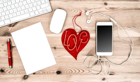 articulos de oficina: Oficina Lugar de trabajo con el corazón rojo, teclado, Tablet PC, teléfono, auriculares. concepto de día de San Valentín