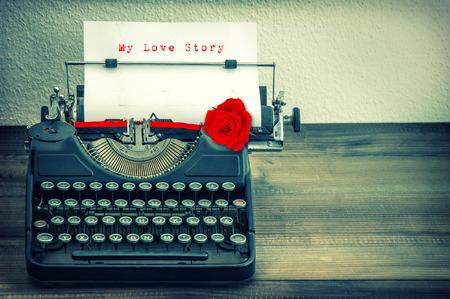 PAPIER A LETTRE: Machine à écrire vintage avec du papier blanc et rouge fleur rose. Exemple de texte Mon Love Story. Vintage style grungy image tonique