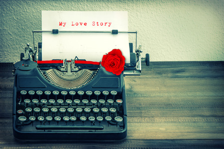 Vintage typewriter with white paper and red rose flower. Sample text My Love Story. Vintage style toned grungy picture