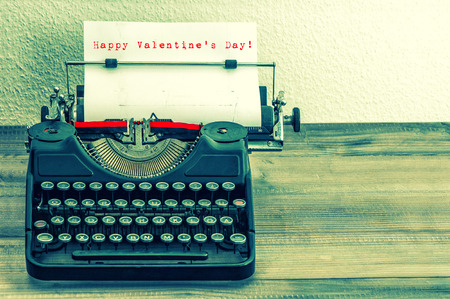 Typewriter with white paper page on wooden table. Sample text Happy Valentine photo
