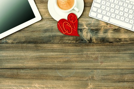 Red love heart, tablet pc, keyboard and coffee on wooden table. Valentines Day workplace. Retro style toned picture photo