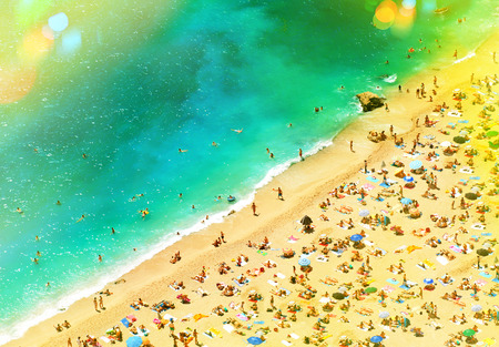 sunbeds: Beach with tourists, sunbeds and umbrellas. Sea travel destination. Holidays background with light leaks and lens flares