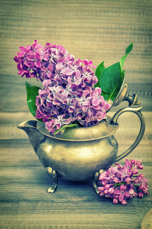 antique vase: Lilac flowers in antique vase on wooden background. Vintage style toned picture