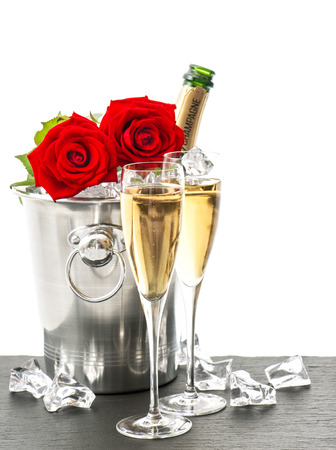 romantic dinner: Champagne, two glasses and red roses. Festive arrangement with sparkling wine and flowers