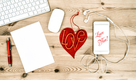 working place: Office Working Place with Red Heart, Keyboard, Tablet PC, Phone. Valentines Day concept. Sample text Love You! Stock Photo