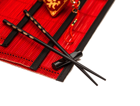 lucky charm: Black chopsticks on red bamboo mat. Asian style table place setting with chinese new years lucky charm
