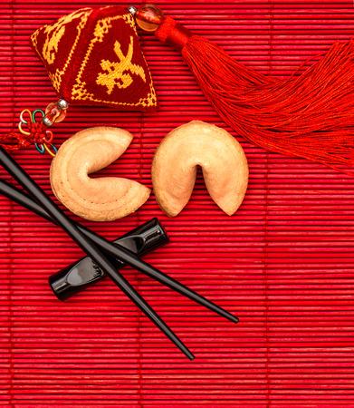 Amuleto de la suerte, galletas de la fortuna y palillos. Año Nuevo chino fondo rojo Foto de archivo - 39171750