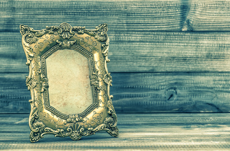 Baroque picture frame: Golden baroque picture frame on wooden background. Retro style toned picture