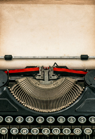 Antique typewriter with aged textured paper sheet. Space for your text