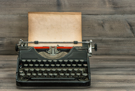 antique typewriter with grungy textured paper page on wooden table. vintage style still life photo