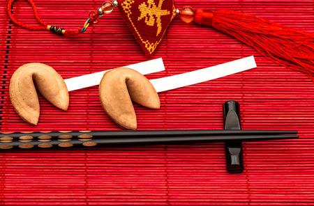 arroz chino: A�os nuevos chinos encanto suerte, galletas de la fortuna y palillos negros en la estera de bamb� rojo