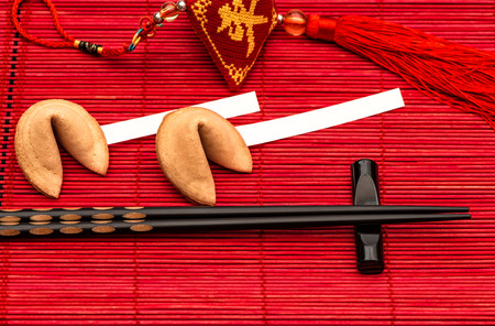 chinese new year food: Chinese new years lucky charm, fortune cookies and black chopsticks on red bamboo mat