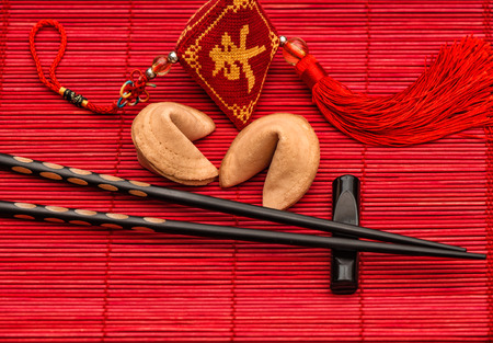 Festive asia style background with lucky charm, fortune cookies and black chopsticks on red bamboo mat. Chinese new year concept Standard-Bild