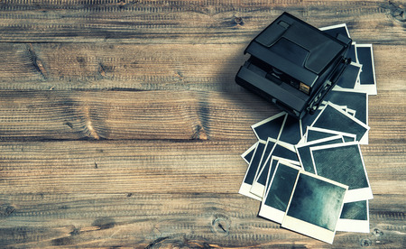 old photo frames and camera on rustic wooden background. retro style toned picture