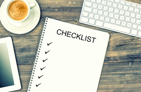checklist: Notebook, digital tablet pc, keyboard and coffee on wooden background. Mock up in style with sample text Checklist