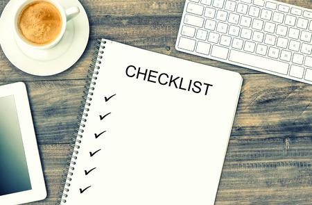 Notebook, digitale tablet pc, toetsenbord en koffie op houten achtergrond. Mock-up in stijl met voorbeeldtekst Checklist
