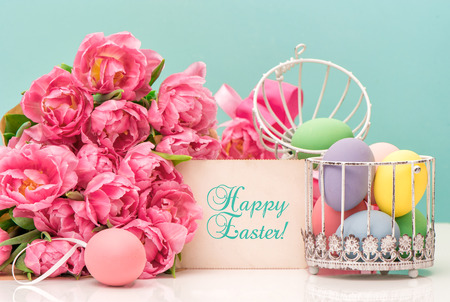 Tulip flowers and pastel colored easter eggs. Festive decoration with greetings card and sample text Happy Easter! photo
