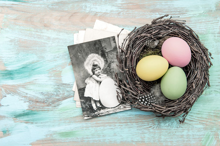 nostalgic: Easter eggs in nest and antique greetings card. Nostalgic retro style toned picture