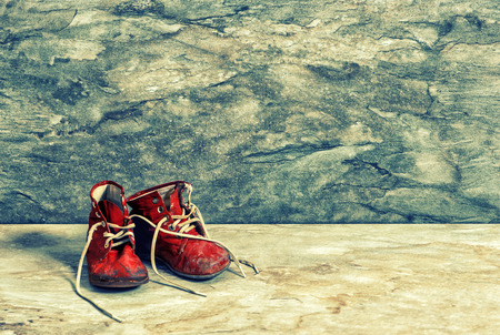 baby shoes: Antique red baby shoes on rustic background.