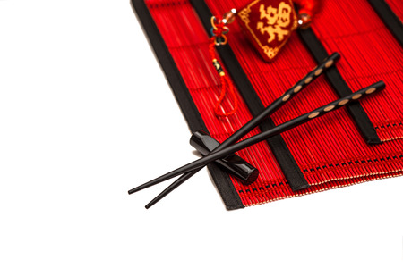 Black chopsticks on red bamboo mat. Asian style table place setting with chinese new year ornament. Lucky charm
