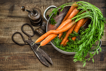 stile country: Fresh carrots with greens and vintage kitchen utensils on wooden background. Country style food concept Archivio Fotografico