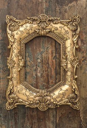 antique frames: Vintage golden frame on wooden background. Grunge wood texture Stock Photo