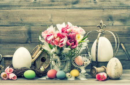 Stil: Easter stil life. Decoration with tulip flowers and colored eggs. Vintage style toned picture