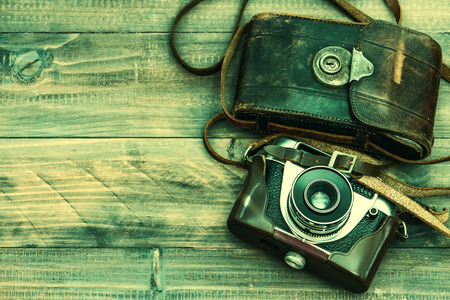 analogous: Vintage film photo camera with leather bag on wooden background. Top view. Retro style toned picture