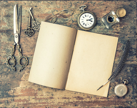 picture person: Open journal book and vintage writing tools on wooden table. Feather pen, inkwell, keys on textured background. Retro style toned picture