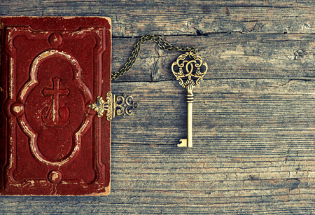Antique bible book and golden key on wooden background. Vintage still life