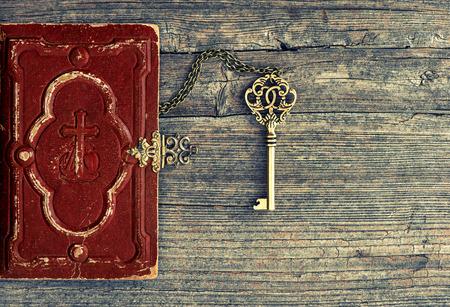 biblia: Biblia antiguo y llave de oro sobre fondo de madera. Bodegón vintage Foto de archivo