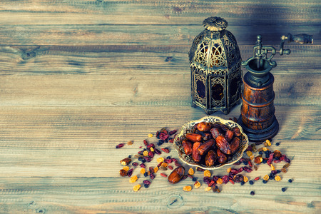 Raisins and dates on wooden background. Still life with vintage oriental lantern. Retro style toned picture Stockfoto