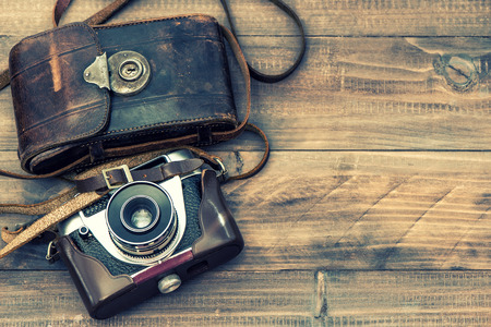 leather bag: Vintage film photo camera with leather bag on wooden background. Top view. Retro Instagram style toned picture
