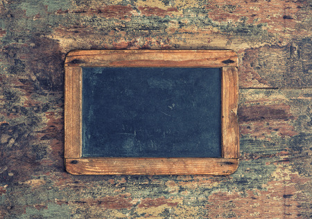 antique: Antique chalkboard on wooden texture. Nostalgic background with copy space for your text. Retro style toned picture Stock Photo