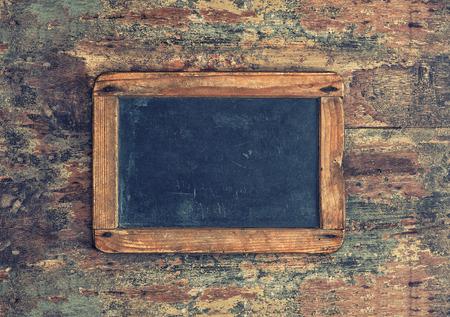 grabado antiguo: Pizarra antigua en la textura de madera. Fondo nostálgico con copia espacio para el texto. Estilo retro tonificado foto Foto de archivo