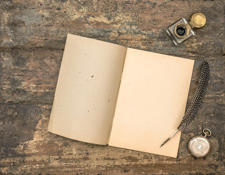 Open diary book and vintage office supplies on wooden table. Feather pen and inkwell on textured background