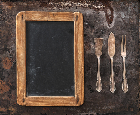 silver cutlery: Antique silver cutlery and blackboard for your text. Retro style toned picture Stock Photo