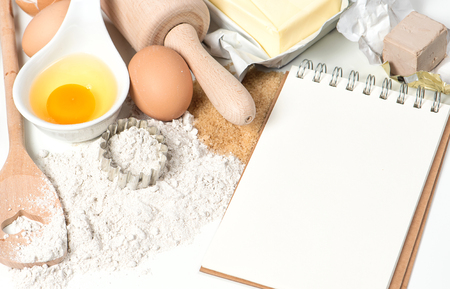 Recipe book and baking ingredients eggs, flour, sugar, butter, yeast. Food background