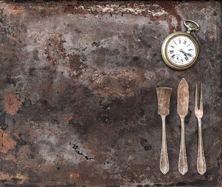 grunge silverware: Vintage silver cutlery and antique pocket watch on rustic textured metal background. Antique tableware