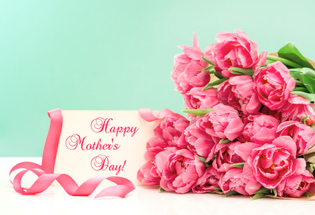 mothers day: Pink tulips and greeting card with sample text Happy Mothers Day! Stock Photo