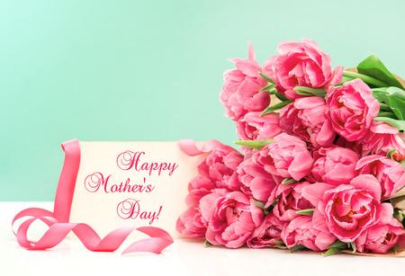 tarjeta postal: Tulipanes de color rosa y tarjeta de felicitación con el texto de ejemplo Feliz Día de las Madres! Foto de archivo