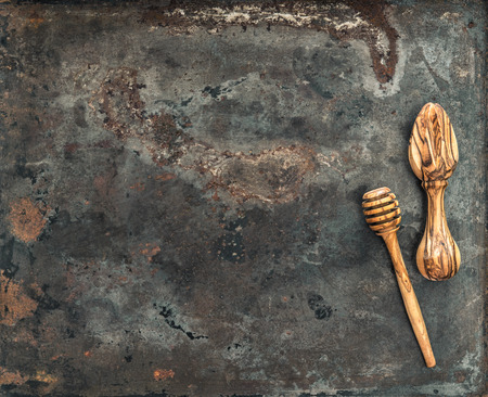 grunge cutlery: Wooden kitchen utensils on rusted metal plate background. Vintage tools concept Stock Photo