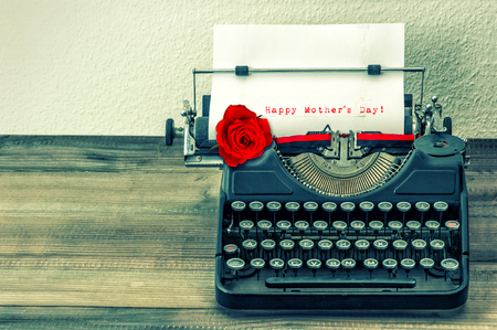 Vintage typewriter with white page and red rose flower. Sample text Happy Mothers Day! Reklamní fotografie