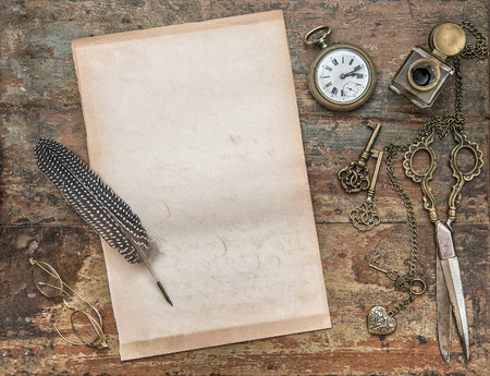 feather pen: Letter paper and vintage writing tools. Feather pen, inkwell, keys on textured wooden background. Retro style toned picture