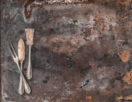 silver cutlery: Vintage silver cutlery on rustic textured metal background. Antique tableware Stock Photo