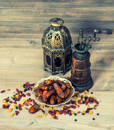food still: Still life with vintage oriental lantern and mill. Raisins and dates on wooden background. Creative food