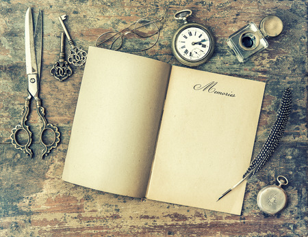 feather pen: Paper page and vintage writing tools. Feather pen, inkwell, keys on textured wooden background. Memories. Retro style toned picture