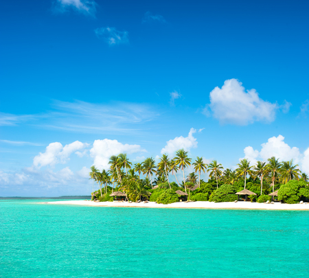 island: Landscape of tropical island beach with palm trees and cloudy blue sky Stock Photo