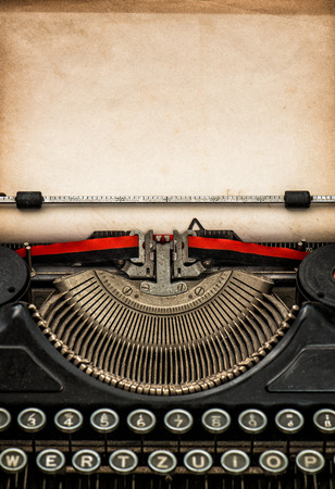 vintage typewriter: Antique typewriter with aged textured paper sheet with space for your text Stock Photo