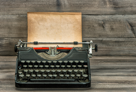 Antique typewriter with old textured paper page on wooden table. Vintage style toned picture